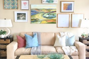 A bright and cheerful family room showcases a colorful gallery wall behind the cream colored couch.