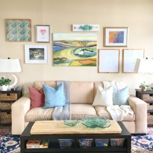 The interior design of this bright and cheerful family room showcases a colorful gallery wall behind the cream colored couch.