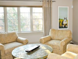 The interior design of this gorgeous light-filled lounge area showcases a row of large windows and a framed art print of a black and white terrier dog.