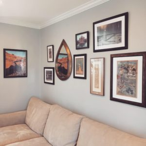The modern interior design of this room showcases a gallery wall with several framed art pieces of varying sizes and a teardrop shaped mirror.