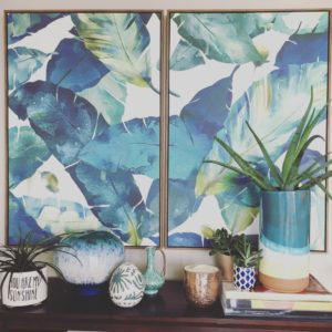 Behind a shelf of potted succulents and sculptural objects, two large framed canvases hang side by side and depict oversized, tropical foliage.