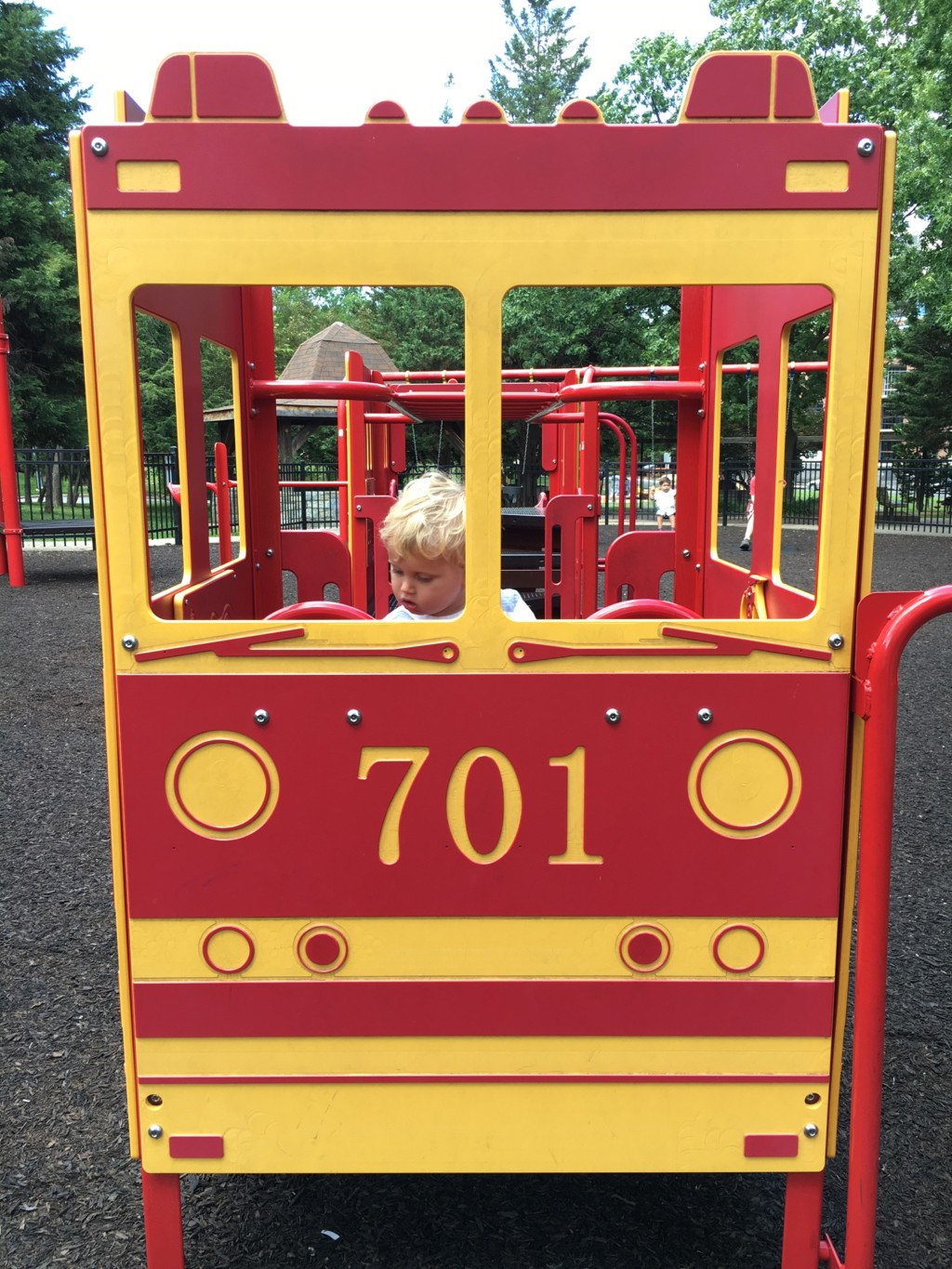 At a playground, a toddler sits behind the steering wheel of a large bright red and yellow fire engine.