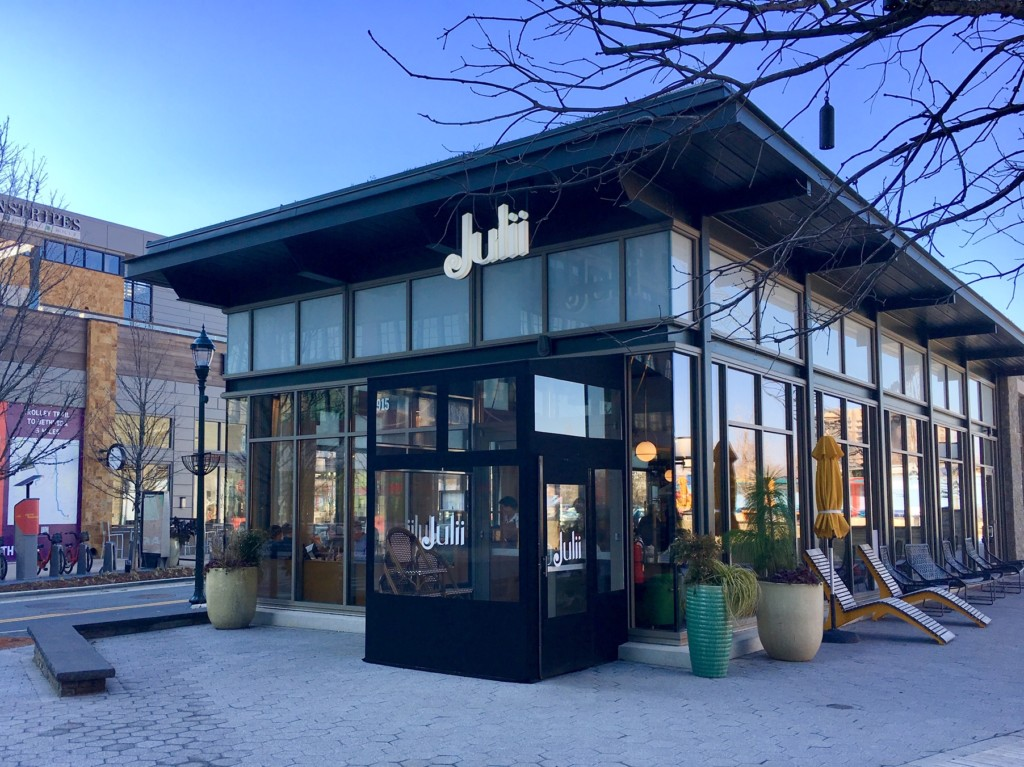 An exterior view of Julii, an intimate restaurant located in the Pike and Rose development, that stands out architecturally for its use of eye-catching floor to ceiling windows.