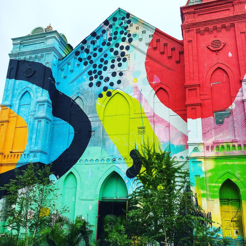 The brick exterior of a historic church building has been completely painted over with a colorful abstract mural by the artist HENSE.