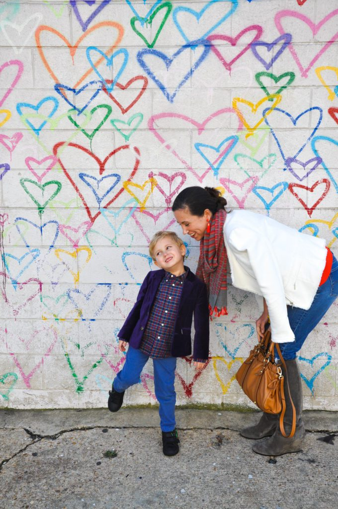A smiling mother bends down towards her young son, while standing in front of a mural of multicolored hearts.