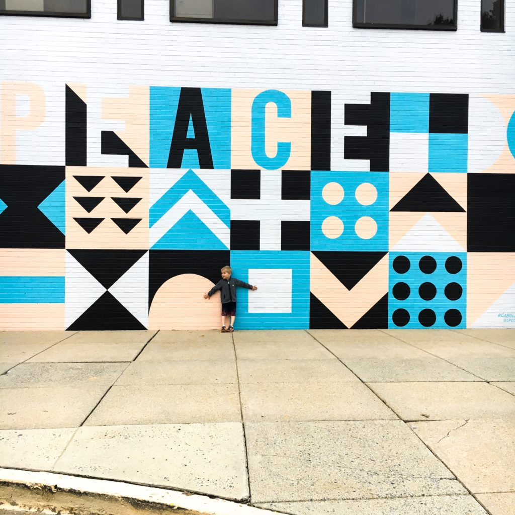 A young boy stands with his back against a large scale mural that reads P-E-A-C-E.