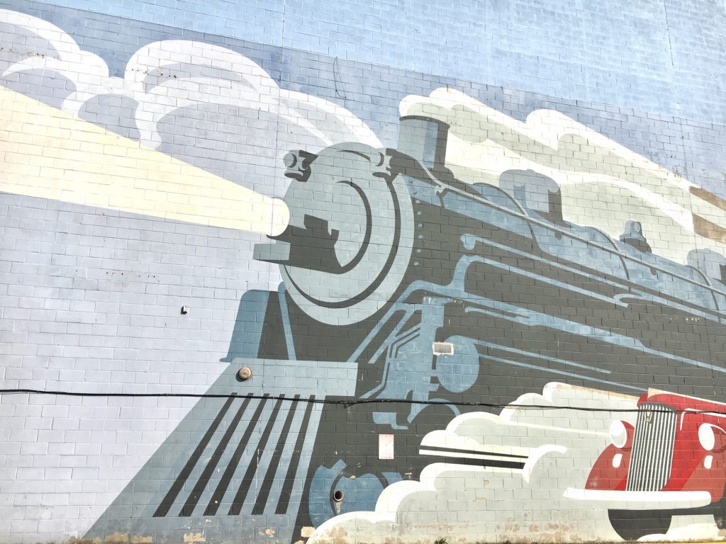 A large scale mural of a steam engine train and a red classic car are painted on the side of a building's brick wall.