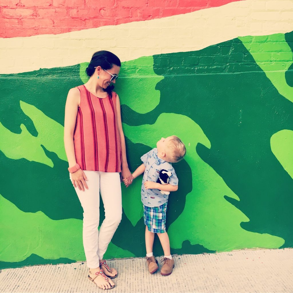 A mother and young son hold hands in front of the Watermelon House mural in Washington DC.