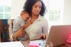 Mother With Baby Working In Office At Home