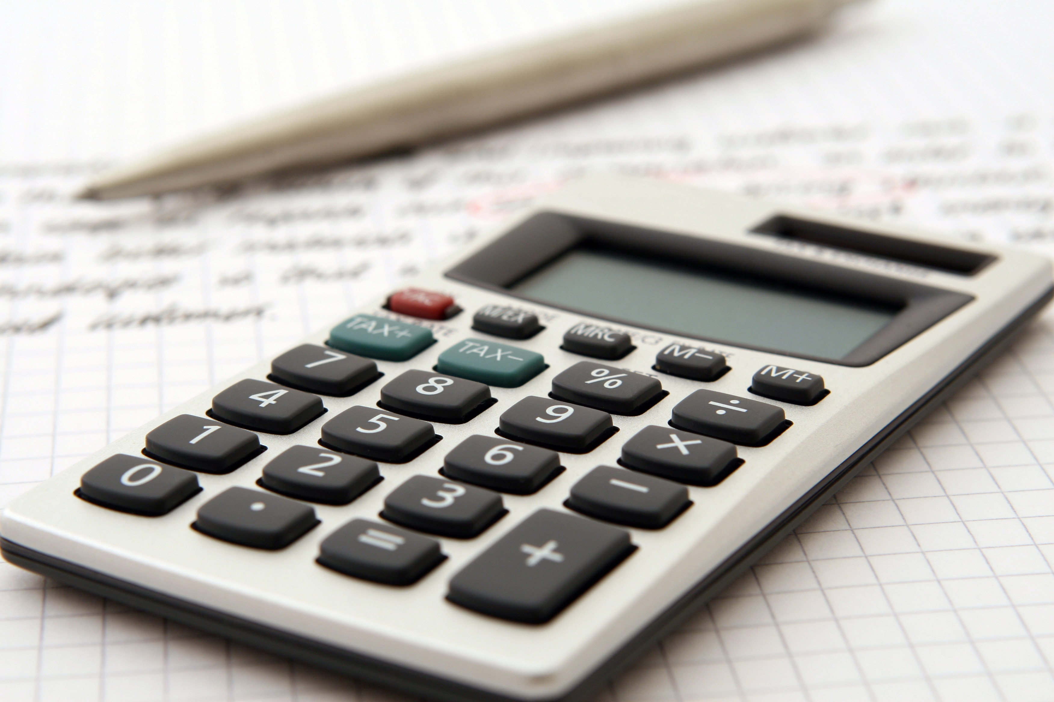 A calculator, pen, and paper convey the need to assess one's personal finances when considering saving for college.