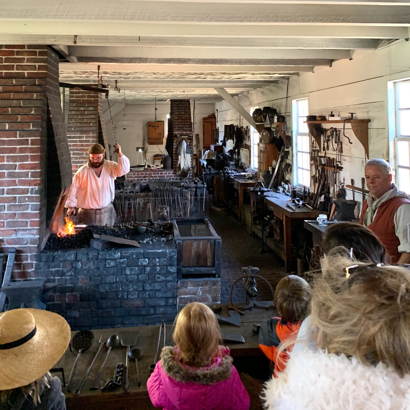 Onlookers watch as a blacksmith dressed in authentic period attire works in this historic, revolutionary era metal workshop.