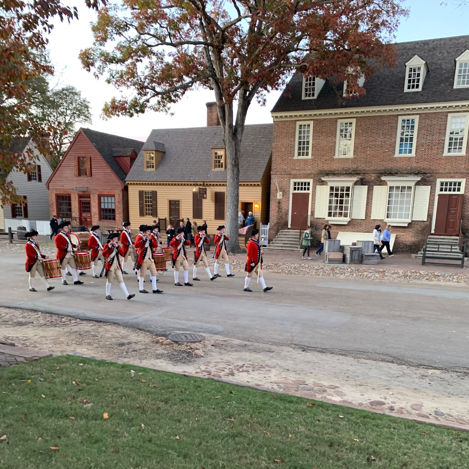 The Colonial Williamsburg Fifes and Drums march down the street wearing the distinctive red coats of British military uniforms.