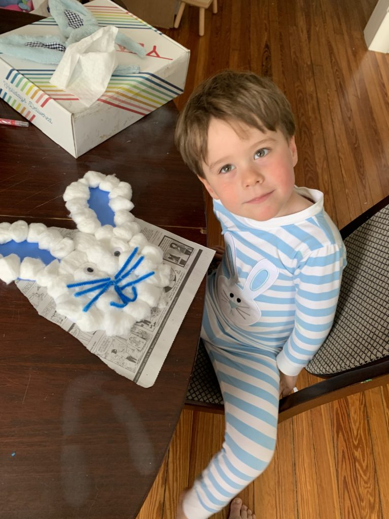 Boy shows Easter bunny craft made from cotton balls.