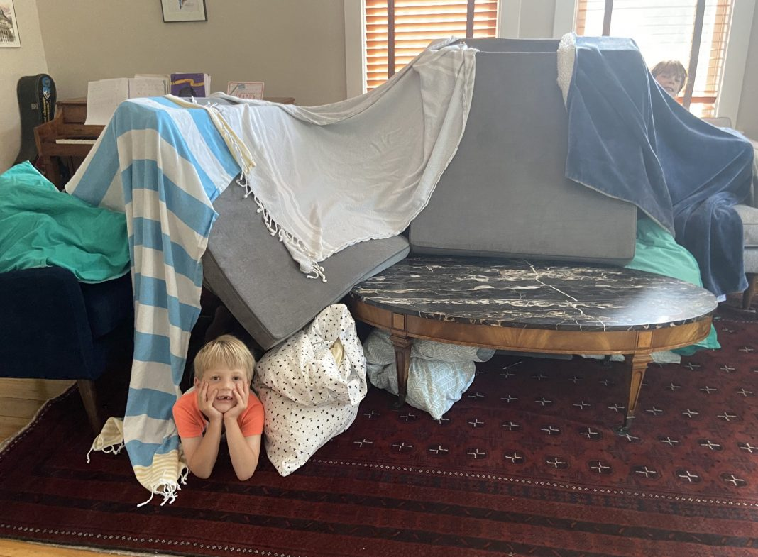 This photo shows how children propped cushions on a sofa and draped towels over them to make a tent in their living room.
