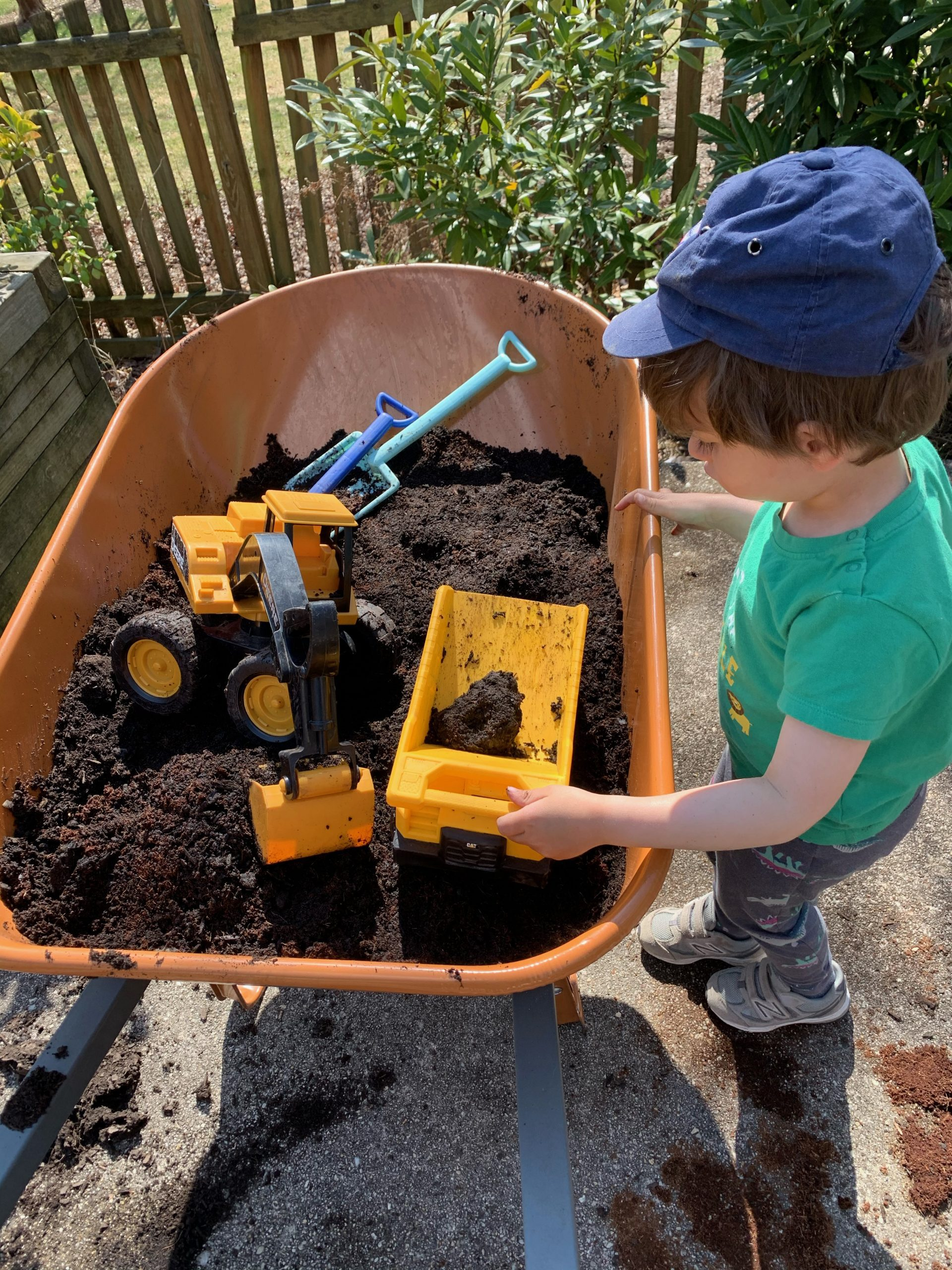 A young boy looks at his toys in a wheelbarrow full of dirt.